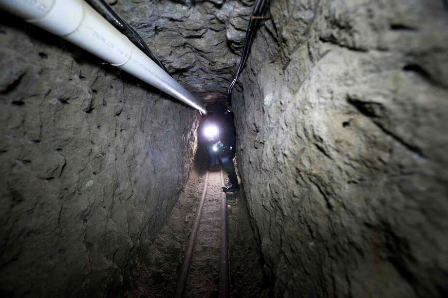 """Police on Thursday examine the tunnel where drug lord Joaquin """"El Chapo"""" Guzman made his escape from the Altiplano maximum security prison in Almoloya, west of Mexico City. At least 18 minutes had elapsed last Satuday before authorities realized their most-prized prisoner slipped into a mile-long tunnel. Photo: Marco Ugarte, STR / AP"""