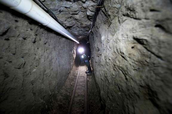 """Police on Thursday examine the tunnel where drug lord Joaquin """"El Chapo"""" Guzman made his escape from the Altiplano maximum security prison in Almoloya, west of Mexico City. At least 18 minutes had elapsed last Satuday before authorities realized their most-prized prisoner slipped into a mile-long tunnel."""