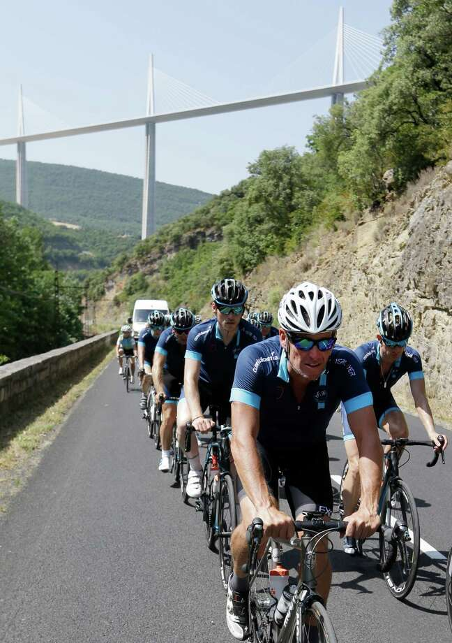 "Lance Armstrong leads a pack of riders near the Viaduc de Millau, seen behind, during the charity ride ""Le Tour, One Day Ahead,"" between Rodez and Mende, southern France, Friday July 17, 2015. While the Tour de France is going on, Armstrong takes part to a charity ride called ""Le tour-One Day Ahead"" with the goal of raising money to cure Leukemia. (AP Photo/Lionel Cironneau) ORG XMIT: PAR110 Photo: Lionel Cironneau / AP"