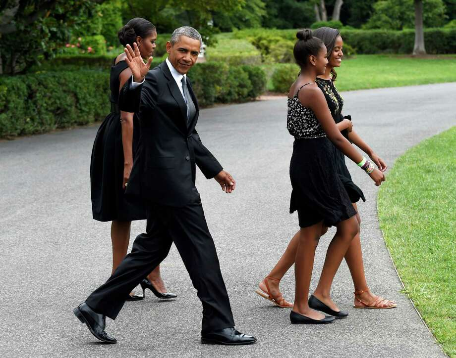 FILE - In this Aug. 30, 2014 file photo, President Barack Obama, accompanied by first lady Michelle Obama, waves as they follow their daughters Sasha, second from right, and Malia out of the White House in Washington. President Barack Obama is headed to New York for a rare father-daughter weekend in the city. He'll also collect some cash for Democrats while he's there.  (AP Photo/Susan Walsh, File) ORG XMIT: WX105 Photo: Susan Walsh / AP