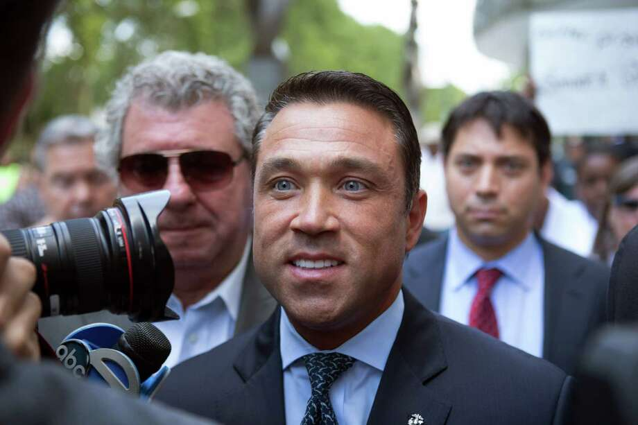 Former U.S. Rep. Michael Grimm, center, leaves following his sentencing at federal court Friday, July 17, 2015, in the Brooklyn borough of New York.  Grimm was sentenced to 8 months in prison on Friday for tax evasion.  (AP Photo/Kevin Hagen) ORG XMIT: NYKH202 Photo: Kevin Hagen / FR170574 AP
