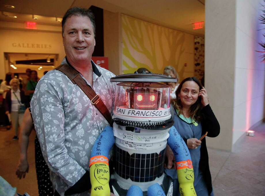 Co-creator David Harris Smith carries hitchBOT, a hitchhiking robot, during its introduction to an American audience Thursday at the Peabody Essex Museum in Salem, Mass. HitchBOT is setting out with San Francisco as its destination. Photo: Stephan Savoia, STF / AP
