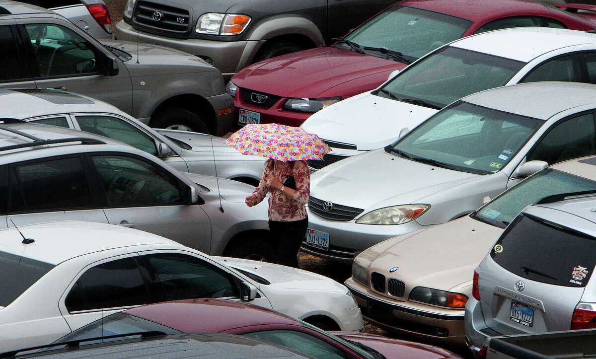 A woman shields herself from the rain as she walks through a parking lot on Milam Street, Wednesday, Feb. 6, 2013, in Houston. (Cody Duty / Houston Chronicle)