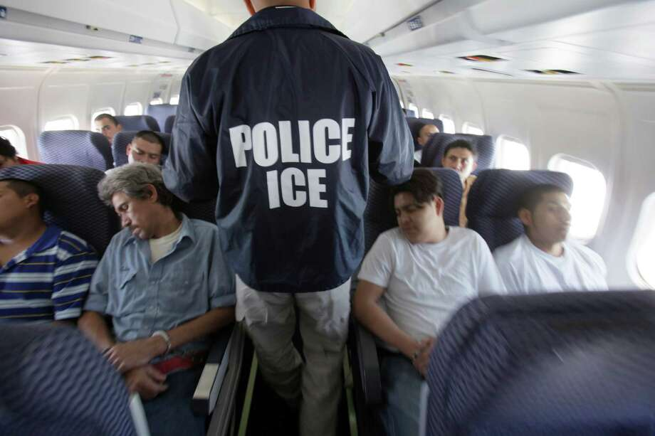FILE - In this May 25, 2010 file photo, an Immigration and Customs Enforcement agent walks down the aisle among shackled Mexican immigrants a boarded a U.S. Immigration and Customs Enforcement charter jet for deportation in the air between Chicago, Il. and Harlingen, Texas. A Homeland Security Department internal watchdog says U.S. Immigration and Customs Enforcement could have saved millions of dollars on charter flights carrying deported immigrants to their home countries by not leaving seats empty. (AP Photo/LM Otero, File) Photo: LM Otero, STF / AP