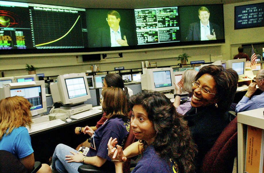 FILE - In this Sept. 21, 2003, file photo, Claudia Alexander, right, project manager for Galileo, waits in the mission control room in Pasadena, Calif., along with engineer Nagin Cox, center, and others for the spacecraft to take its final plunge into Jupiter. Alexander, a pioneering scientist who helped direct NASA's Galileo mission to Jupiter and the international Rosetta space exploration project, has died Saturday, July 11, 2015, after a long battle with breast cancer. She was 56. (AP Photo/Ric Francis, File) Photo: Ric Francis, STF / AP