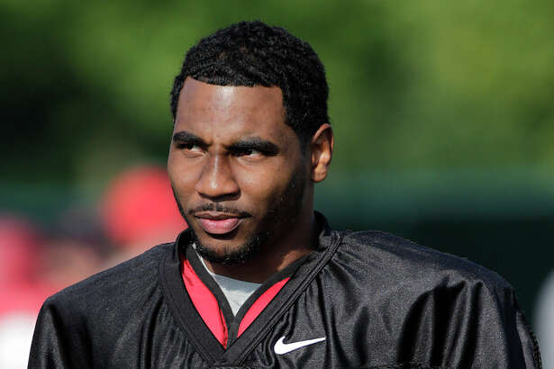 In this Aug. 9, 2014, file photo, Ohio State quarterback Braxton Miller watches teammates warm up during an NCAA college football practice in Columbus, Ohio. Miller, among the top contenders for the Heisman Trophy, reportedly reinjured his throwing shoulder during practice. The report about the two-time Big Ten offensive player of the year comes with just more than two weeks before the No. 5 Buckeyes open the season. (AP Photo/Jay LaPrete, File)