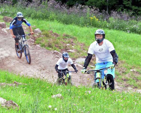 Nils Kajtebeast of Amsterdam, The Netherlands, right, leads his son Kaj, 12, and park instructor Baily Emerton, left, down Wilderness Roll in Windham Mountain Resort's new mountain bike park Friday July 17, 2015 in Windham, NY.  (John Carl D'Annibale / Times Union) Photo: John Carl D'Annibale / 00032665A