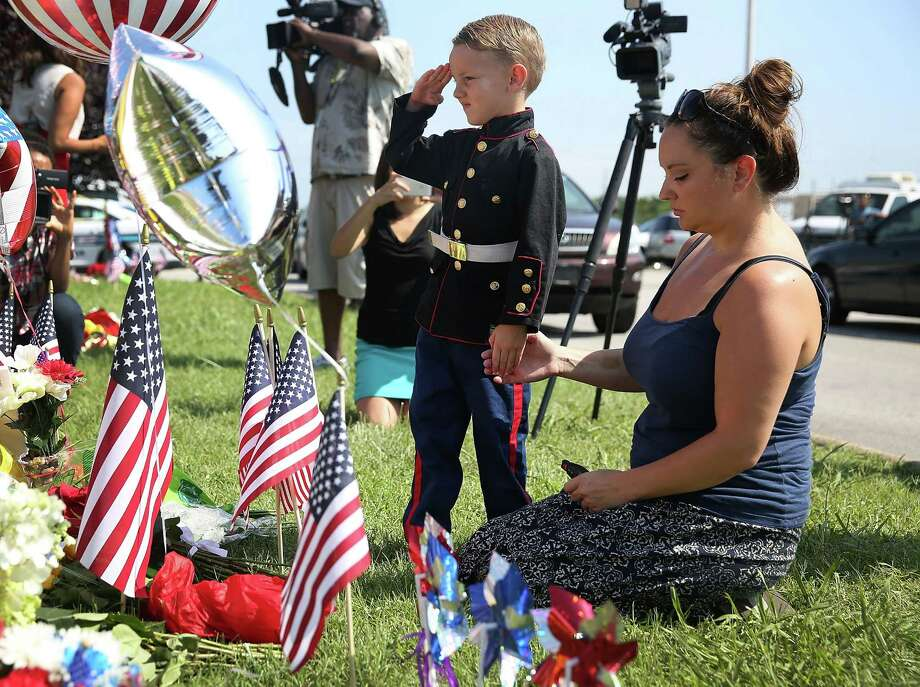 CHATTANOOGA, TN - JULY 17:  Blake Miller and his mother, Ashley Miller whose husband is a Lieutenant in the Marine Corps pay their respects to those killed while visiting a memorial placed in front of the Armed Forces Career Center/National Guard Recruitment Office which had been shot up on July 17, 2015 in Chattanooga, Tennessee. According to reports, Mohammod Youssuf Abdulazeez, 24, opened fire on the military recruiting station at the strip mall and then drove to an operational support center operated by the U.S. Navy more than seven miles away and killed four United States Marines there.  (Photo by Joe Raedle/Getty Images) ORG XMIT: 565316685 Photo: Joe Raedle / 2015 Getty Images