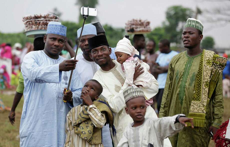 A Nigeria Muslim family takes a selfie portrait before Eid al-Fitr prayer, marking the end of the Muslim holy fasting month of Ramadan in Lagos, Nigeria, Friday, July 17, 2015. (AP Photo/Sunday Alamba) ORG XMIT: XSA111 Photo: Sunday Alamba / AP