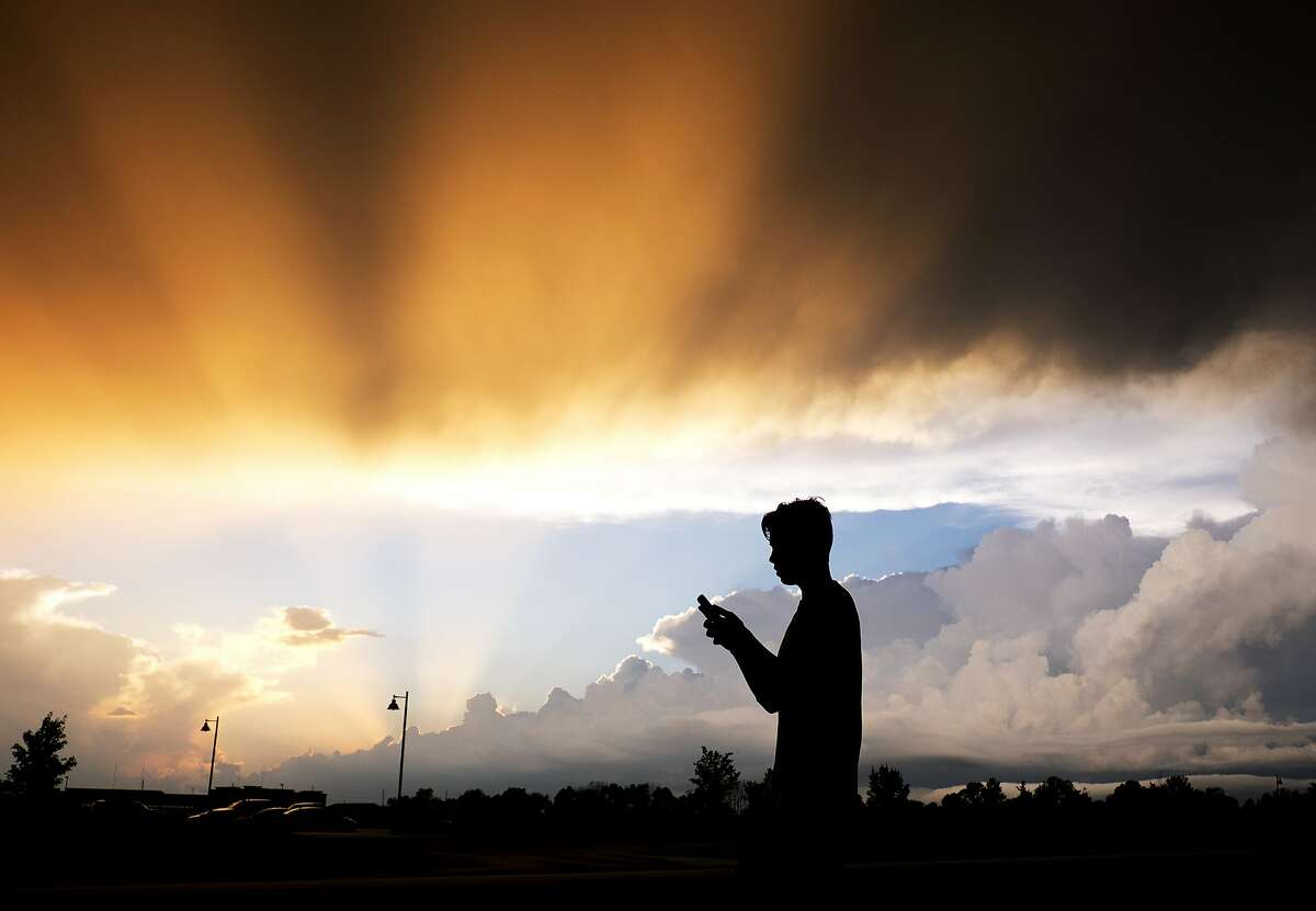 A teenager checks his cell phone as storm clouds pass Friday, July 17, 2015, in Zionsville, Ind. Scattered storms were in the forecast for most of Friday evening. (AP Photo/Darron Cummings)