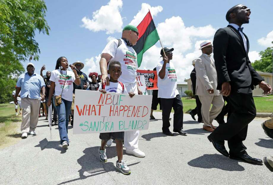Protesters Kofi Taharka and William Mitchell IV, 5, march along with others questioning the death of Sandra Bland from Waller County Jail to the Waller County Courthouse in Hempstead. Photo: Melissa Phillip /Houston Chronicle / © 2015  Houston Chronicle