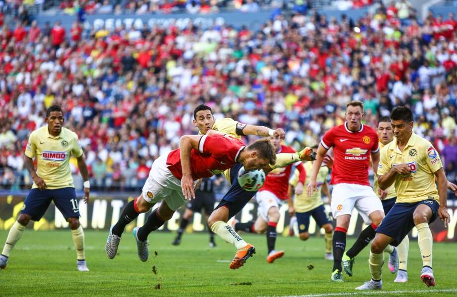 Manchester United player Michael Carrick goes airborne after colliding with Club America players during the International Champions Cup soccer match at CenturyLink Field on Friday, July 17, 2015.  (Joshua Trujillo, seattlepi.com) Photo: JOSHUA TRUJILLO, SEATTLEPI.COM