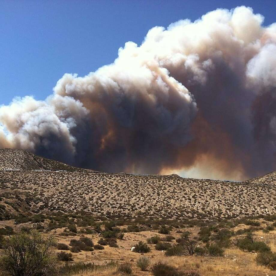 Smoke from a wildfire rises above Interstate 15 on the Cajon Pass, Friday, July 17, 2015, near San Bernadino, Calif., as a fast-moving wildfire swept across the Southern California freeway, destroying numerous vehicles and sending motorists running to safety before burning at least five homes.  Photo: Arsenio Alcantar, Associated Press
