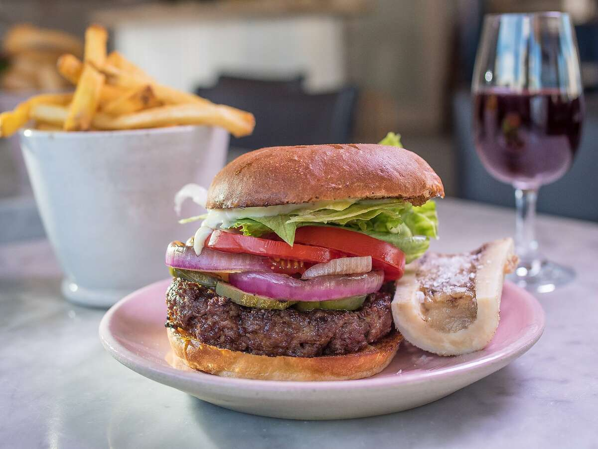 The Kronnerburger with bone marrow, fries, and a glass of red wine at Kronnerburger in Oakland, Calif., is seen on July 17th, 2015.