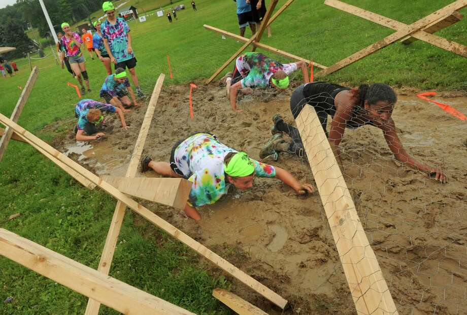 Participants crawl through a mud pit during the Maple Ski Ridge 5k Mud Run on Saturday July 18, 2015 in Schenectady, N.Y. (Michael P. Farrell/Times Union) Photo: Michael P. Farrell / 00032662A