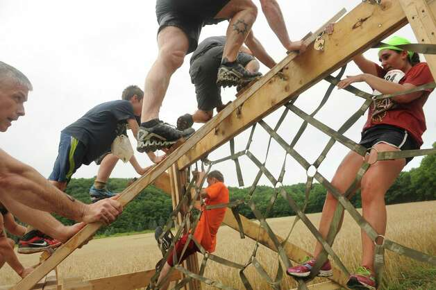Participants climb an obstacle during the Maple Ski Ridge 5k Mud Run on Saturday July 18, 2015 in Schenectady, N.Y. (Michael P. Farrell/Times Union) Photo: Michael P. Farrell / 00032662A
