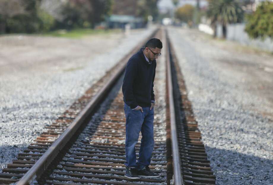 Kristian Ramiriez stands on the railroad tracks on Dec. 19, 2014 near the site off Downey Avenue in Paramount, Calif., where his brother Oscar Ramirez was shot and killed by deputies in October. (Mark Boster/Los Angeles Times/TNS) Photo: Mark Boster, McClatchy-Tribune News Service