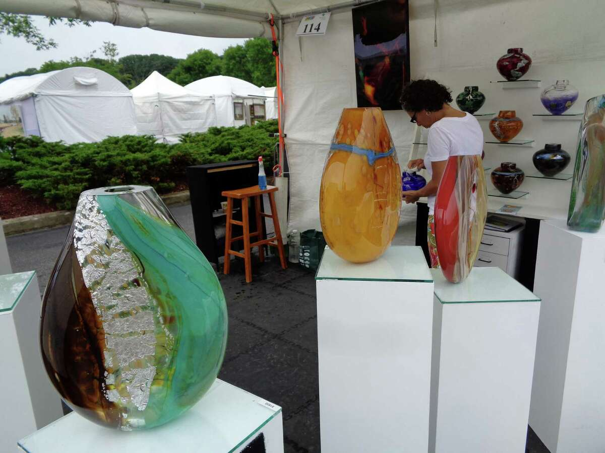 Randi Solin of Solin Glass in Brattleboro, Vt., polishes her blown glass vases in anticipation of the crowds that were slow to come to the 42nd annual Westport Fine Arts Festival on Saturday morning because of rain but turned out in large numbers after the sun broke through early afternoon.