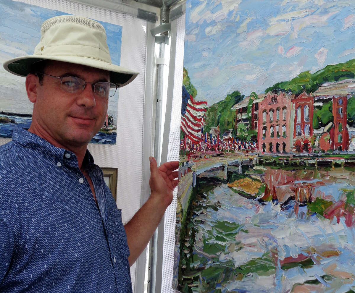 Jim Chillington poses in front of one of his oil paintings of downtown Westport including the Ruth Steinkraus Cohen Bridge and Saugatuck River at the arts festival.