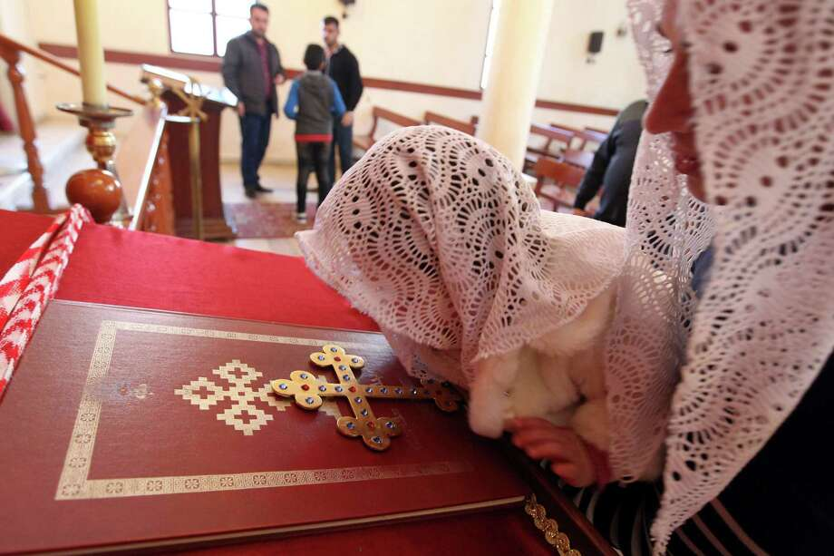 An Assyrian Christian woman and her daughter, who had fled Syria, attend a prayer for 220 Assyrian Christians abducted by Islamic State group jihadists from villages in Syria earlier this year. Christians are encountering increasingly hostile conditions in the Middle East. Photo: ANWAR AMRO /AFP / Getty Images / AFP