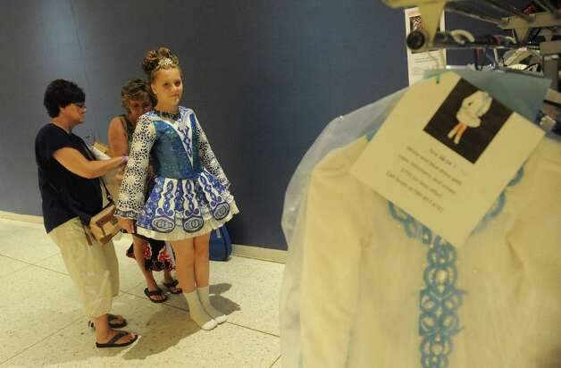 Eleven-year-old Jillian Cola trys on a new dress with the help of her mother Carol Cola and aunt Nancy McKenna during the 27th Annual Governor Thomas Dongan Feis at the Empire State Plaza on Saturday July 18, 2015 in Albany, N.Y. (Michael P. Farrell/Times Union) Photo: Michael P. Farrell / 00032324A