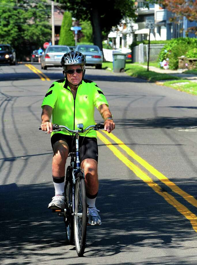 Don Cook, a former Sacred Heart University Director, rides his son Chris' bike along on Grovers Avenue in Bridgeport, Conn., on Thusday July 16, 2015. Chris died at 48 years old of cancer. Don will be riding his son's bike in the upcoming CT Challenge Bike Ride to raise money for a scholarship at SHU in Chris' name. Photo: Christian Abraham / Hearst Connecticut Media / Connecticut Post