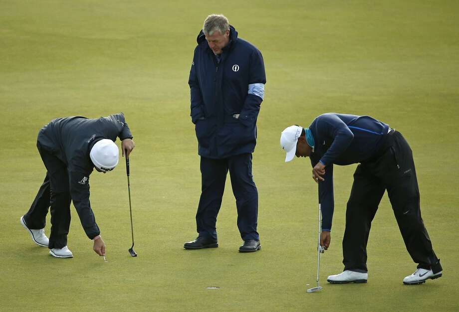 United States' Tiger Woods, right, and South Africa' Louis Oosthuizen, left, mark their balls on the 13th green as an official stops play due to strong winds during the second round of the British Open Golf Championship at the Old Course, St. Andrews, Scotland, Saturday, July 18, 2015. (AP Photo/Jon Super) Photo: Jon Super, Associated Press