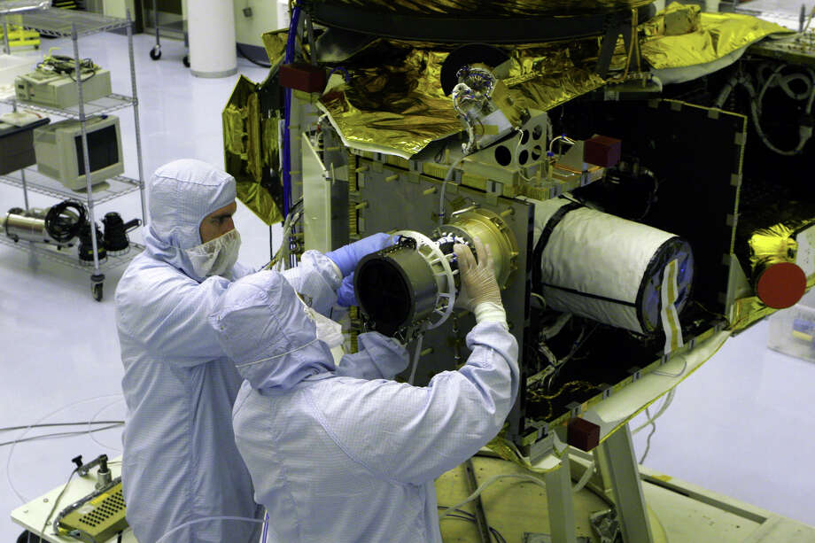 Workers tinker with the Solar Wind Around Pluto instrument on NASA's New Horizons spacecraft. After choosing the New Horizon plan, NASA had just four years and two months to build and launch it before Jupiter passed out of alignment. Photo: NASA, HO / NASA