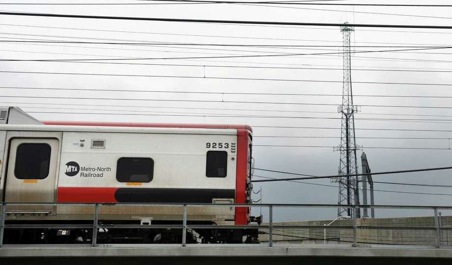 A Metro-North train passes a radio tower in Bridgeport on Wednesday. Photo: Autumn Driscoll / Hearst Connecticut Media / Connecticut Post