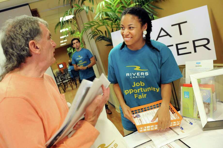Cymone Sammons of the Social Enterprise and Training Center in Schenectady, right, talks with Jonathan Smead of Gloversville during a job fair on Saturday, July 18, 2015, at Schenectady County Community College in Schenectady, N.Y. Rivers Casino and partner organizations were on hand to discuss training and job opportunities in the gaming industry. (Cindy Schultz / Times Union) Photo: Cindy Schultz / 00032607A