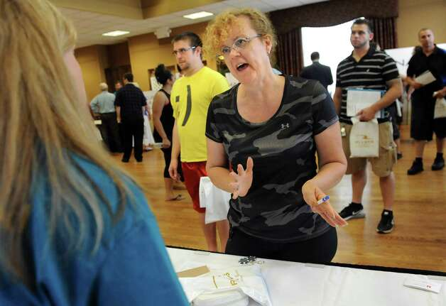 Sue Monteiro of Chatham, center, inquires about opportunities with the Mallozzi Group during a job fair on Saturday, July 18, 2015, at Schenectady County Community College in Schenectady, N.Y. Rivers Casino and partner organizations were on hand to discuss training and job opportunities in the gaming industry. (Cindy Schultz / Times Union) Photo: Cindy Schultz / 00032607A