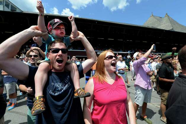 Alex Carey, 2 1/2 sits atop his father Brian's shoulders and is joined by mom, Sara as they route for their horse in the second race of opening day of the 2014 Saratoga Race Course meeting Friday afternoon July 18, 2014 in Saratoga Springs, N.Y.   The Carey's are from Charlotte, N.C. and were visiting inlaws in the Clifton Park area.   (Skip Dickstein / Times Union) Photo: SKIP DICKSTEIN