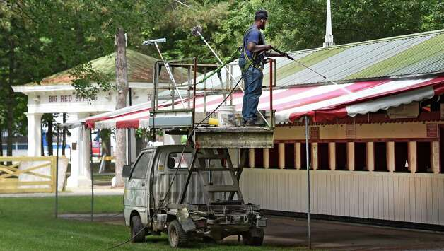 NYRA worker Rashamer Shorter cleans the awnings over the mutuals booths in the picnic area of the Saratoga Race Course Wednesday afternoon July 15, 2015 in preparation for opening day next Friday in Saratoga Springs, N.Y.      (Skip Dickstein/Times Union) Photo: SKIP DICKSTEIN / 00032626A