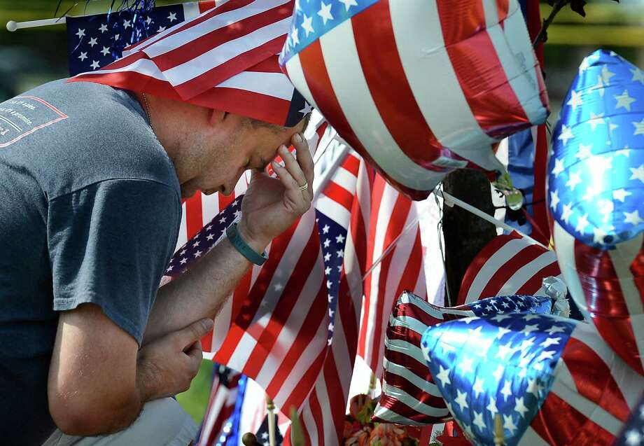 Chris Hollingsworth prays by a makeshift memorial outside the Armed Forces Career Center Saturday, July 18, 2015, in Chattanooga, Tenn. The U.S. Navy says a sailor who was shot in the attack on a military facility in Chattanooga has died, raising the death toll to five people. (AP Photo/Mark Zaleski) ORG XMIT: TNMZ105 Photo: Mark Zaleski / FR170793 AP
