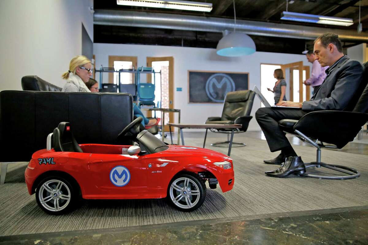 A tiny red car with the MuleSoft logo sits parked next to workers.