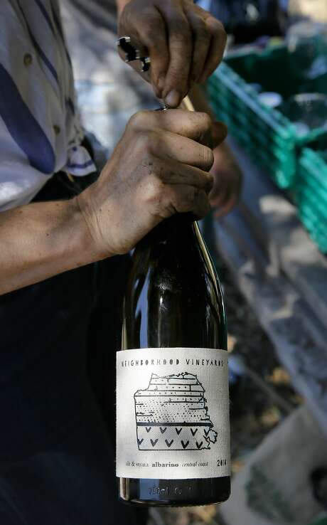 Elly Hartshorn opens a bottle of her albarino wine, for volunteers to taste that came to help out at her small vineyard at Alemany Farm in San Francisco, Calif., as seen on Sat. July 18, 2015. Elly Hartshorn started her vineyard by planting grapes in a slice of parkland above the Alemany Farmers Market, where she volunteered. Photo: Michael Macor, The Chronicle