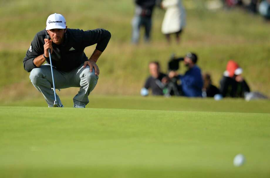 US golfer Dustin Johnson lines up his putt on the 17th green during the completion of his second round 69, on day three of the 2015 British Open Golf Championship on The Old Course at St Andrews in Scotland, on July 18, 2015. American Dustin Johnson birdied the 18th hole to take the outright lead on ten under par at the Open Championship on Saturday after a marathon 10hr 28min delay due to high winds at St Andrews. AFP PHOTO / GLYN KIRKGLYN KIRK/AFP/Getty Images Photo: GLYN KIRK, Stringer / AFP / Getty Images / AFP