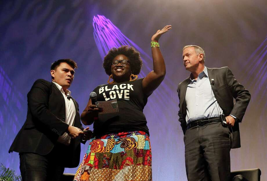 As dozens protesters shout, Tia Oso of the National Coordinator for Black Immigration Network, center, walks up on stage interrupting Democratic presidential candidate, former Maryland Gov. Martin O'Malley, right, as moderator Jose Vargas watches at left, during the Netroots Nation town hall meeting, Saturday, July 18, 2015, in Phoenix. (AP Photo/Ross D. Franklin) Photo: Ross D. Franklin, STF / AP