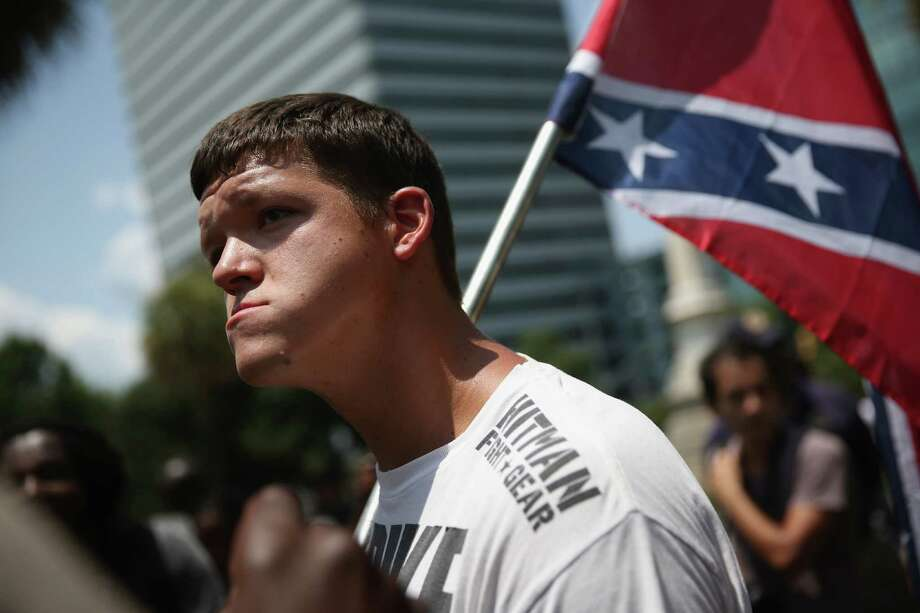 COLUMBIA, SC - JULY 18:  A Ku Klux Klan supporter carries the Confederate flag during a demonstration at the state capitol building on July 18, 2015 in Columbia, South Carolina. Hundreds of people protested the Klan demonstration as law enforcement tried to prevent violence between the opposing groups. Photo: John Moore, Getty Images / 2015 Getty Images