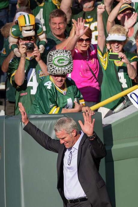 Former Green Bay quarterback Brett Favre receives a warm welcome as he walks onto Lambeau Field for Saturday night's induction into the Packers Hall of Fame. Photo: Mike Roemer, FRE / FR155603 AP