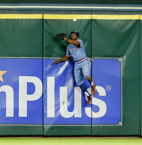 Rangers center fielder Delino DeShields leaps at the wall but can't make the catch on a solo home run by Carlos Correa in the seventh inning Saturday night. Photo: Bob Levey, Stringer / 2015 Getty Images