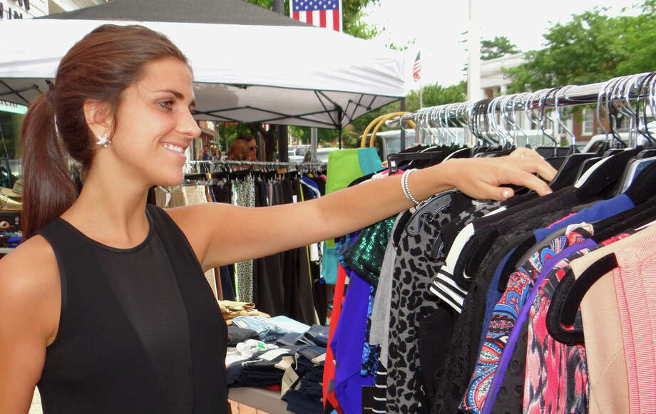 Snappy Gator sales staffer Kendall Stevenson arranges clothes during Fairfield's Sidewalk Sale on Saturday. Photo: Mike Lauterborn / For Hearst Connecticut Media / Fairfield Citizen