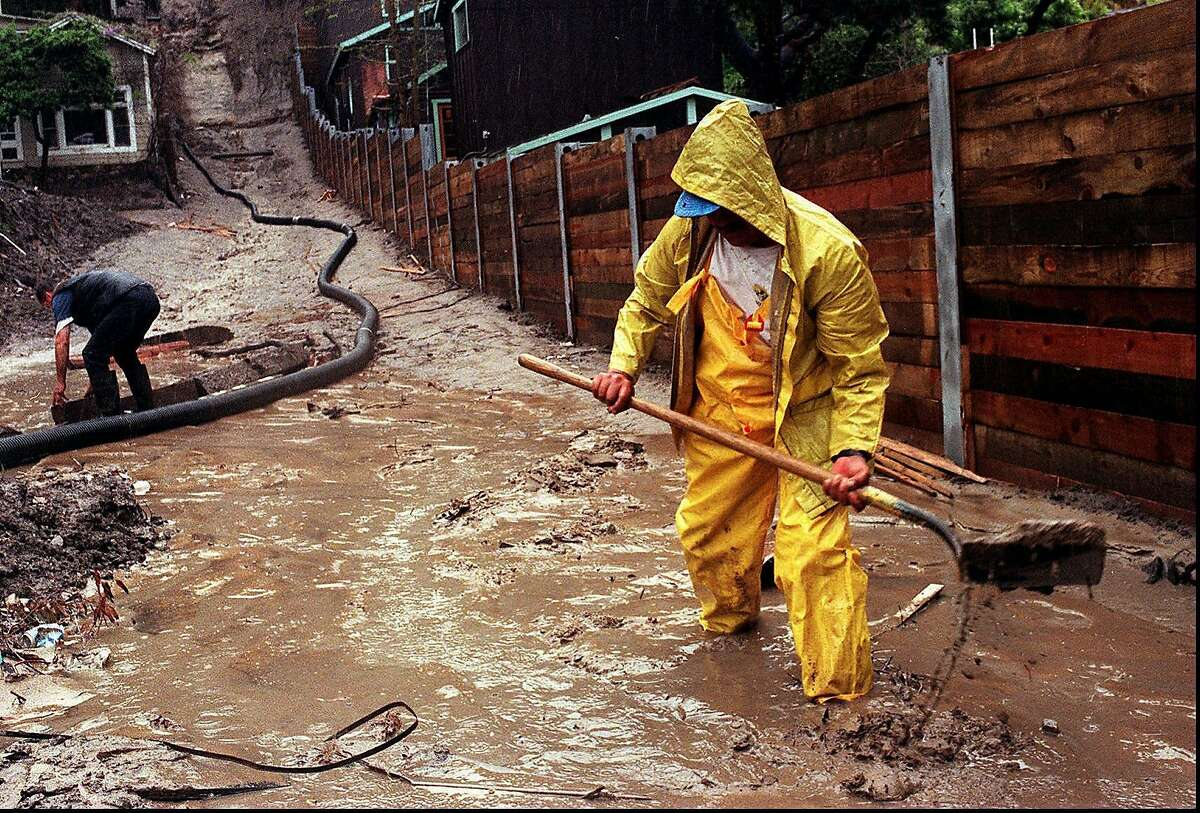 FILE - In this Wednesday, March 25, 1998 file photo, Enrique Lagunas digs a trench to redirect water toward a street in Laguna Beach, Calif. after heavy rains from an El Nino storm hit Southern California. On Thursday, March 6, 2014, the U.S. National Oceanic Atmospheric and Administration announced their prediction of an El Nino warming of the central Pacific Ocean in 2014 that will change weather worldwide. It is expected to trigger fewer Atlantic hurricanes, more rain next winter for drought-struck California and southern states and even cause a milder winter for the nation's cold-struck northern tier next year, meteorologists say. For the world it can mean an even hotter year coming up and food crop losses. (AP Photo/Orange County Register, Bruce Chambers)