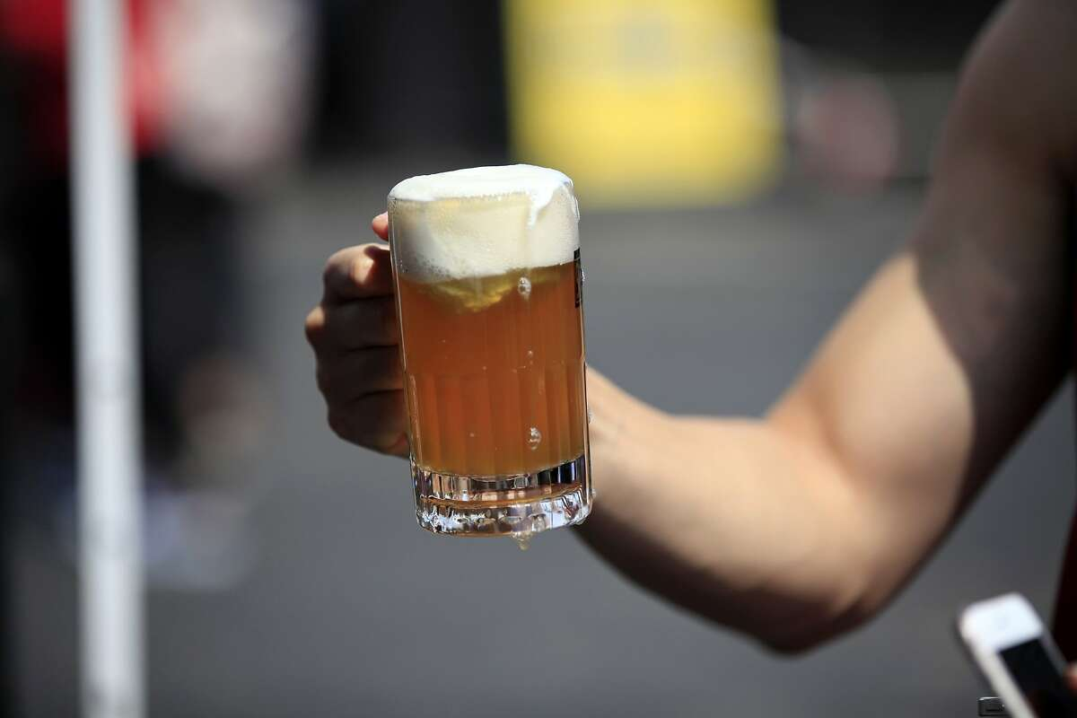 FILE - A man holds a beer float during the National Ice Cream Day Festival at SoMa StrEat Food Park in San Francisco, California, on Sunday, July 19, 2015.