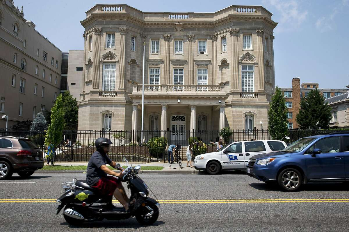 FILE - In this July 1, 2015 file photo a man on a scooter drive past the Cuban Interests Section, which serves as the de facto diplomatic mission of Cuba to the U.S., in Washington. Cuba's blue, red and white-starred flag is set to fly Monday, July 20, outside the country's diplomatic mission in the United States for the first time since the countries severed ties in 1961. (AP Photo/Jacquelyn Martin, File)