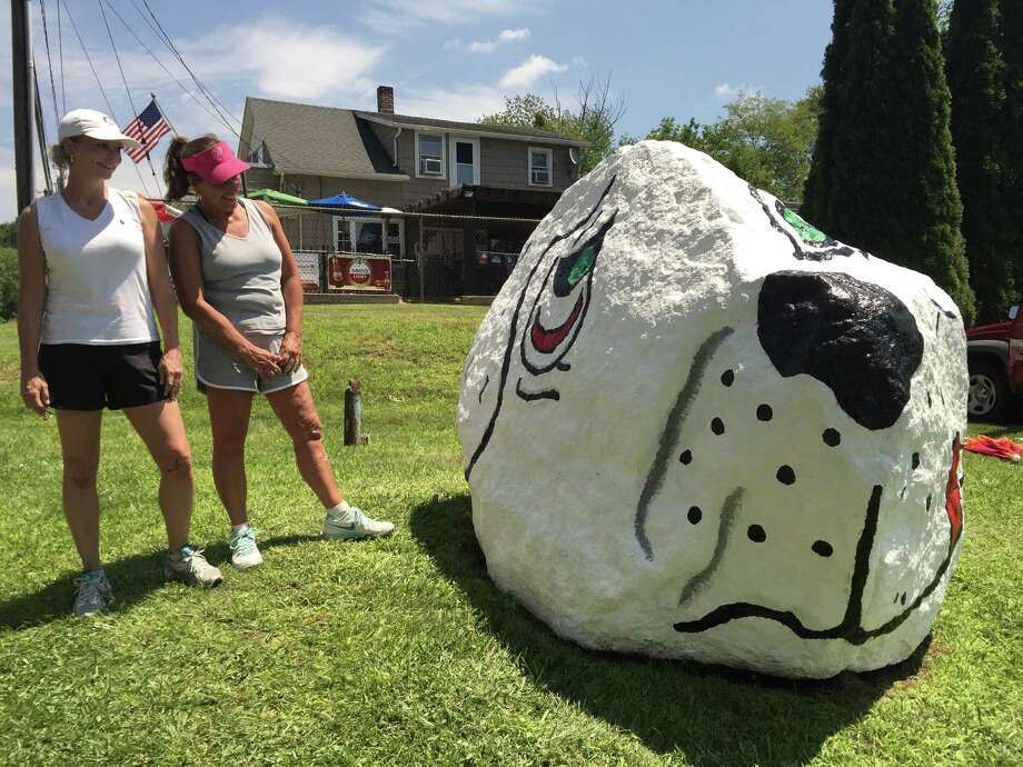 Kim Coleman (left) and Sandy Arconti Atanasoff (right), both of Danbury, take a moment to admire their repainting job on Dog Rock, located across from Candlewood Lake Town Park in Danbury. Photo: / Katrina Koerting