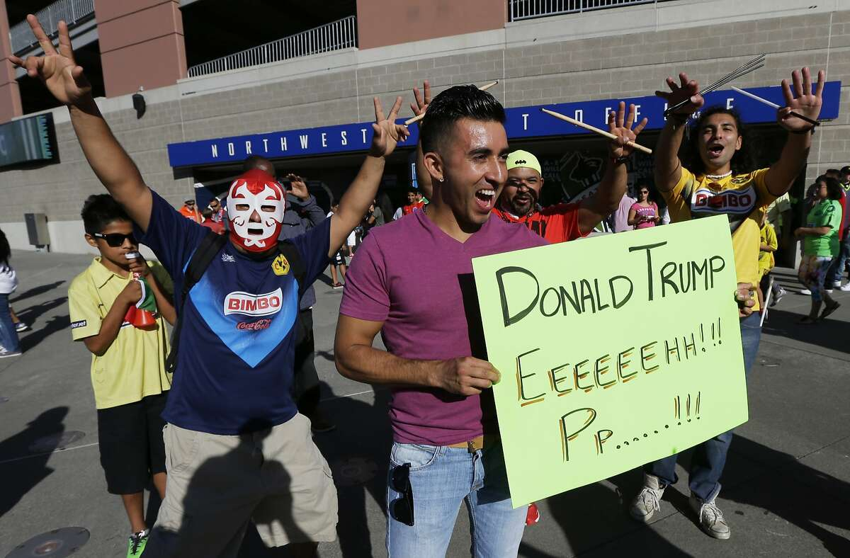 Supporters of Mexico's Club America soccer team hold a sign referring to Republican Presidential hopeful Donald Trump as they cheer for their team outside CenturyLink Field before an international friendly soccer match between Manchester United and Club America, Friday, July 17, 2015, in Seattle. (AP Photo/Ted S. Warren)