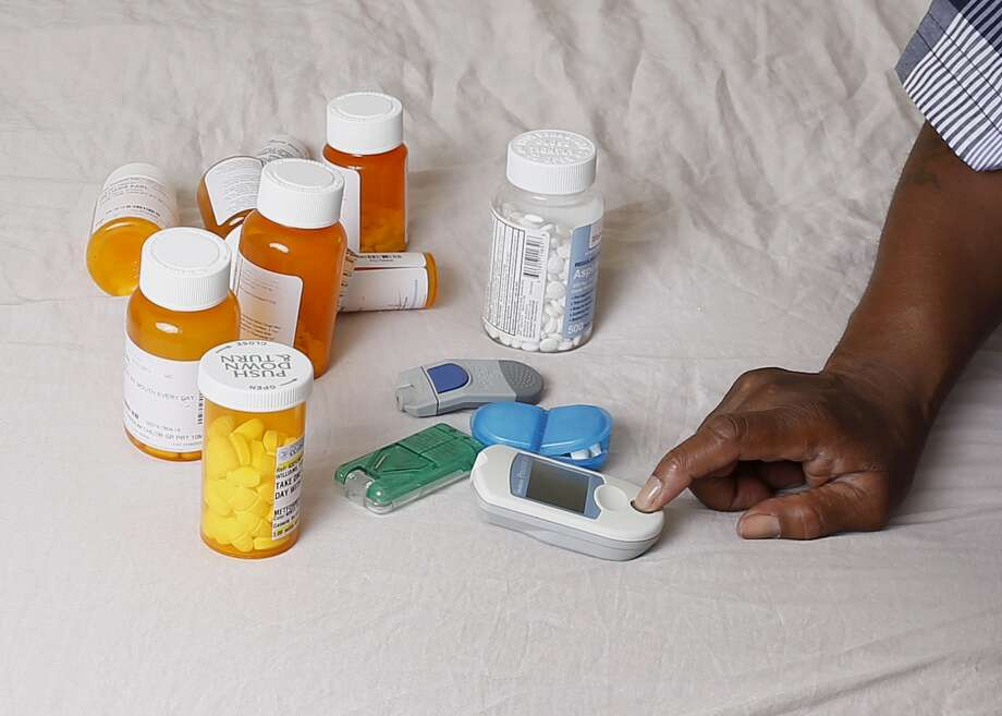 In this Monday, July 13, 2015 photo Earl Charles Williams Sr., 59, sits next to some of the medication he must take for his diabetes in his Chicago home. Williams was uninsured for about a year before a county-run clinic helped him sign up for care under the Affordable Care Act.  More than a dozen states that opted to expand Medicaid under the Affordable Care Act have seen enrollments surge way beyond projections, raising concerns that the added costs will strain their budgets when federal aid is scaled back starting in two years.   (AP Photo/Christian K. Lee) Photo: Christian K. Lee, STF / Associated Press / AP