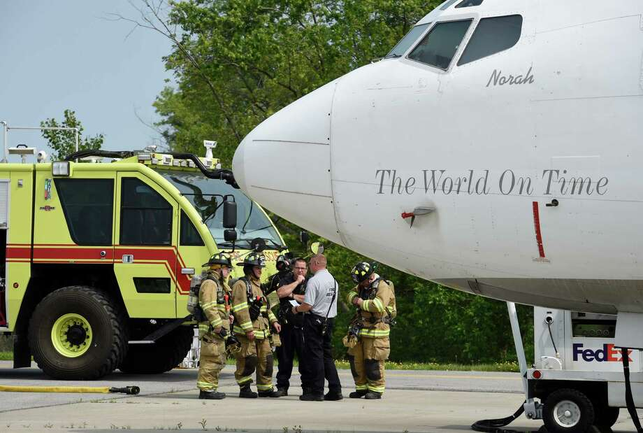 Firefighters discuss their next evolution near a former FedEx Boeing 727 Friday morning, June 12, 2015, which is now a full-time member of the airport fire department after its donation at Albany International Airport  in Colonie, N.Y.  It will be used for fire training evolutions.  (Skip Dickstein/Times Union) Photo: SKIP DICKSTEIN / 00032263A