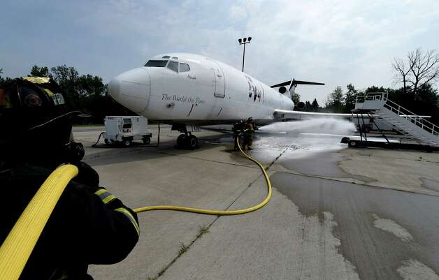 Firefighters foam a former FedEx Boeing 727 Friday morning, June 12, 2015, which is now a full-time member of the airport fire department after its donation at Albany International Airport  in Colonie, N.Y.  It will be used for fire training evolutions.  (Skip Dickstein/Times Union) Photo: SKIP DICKSTEIN / 00032263A